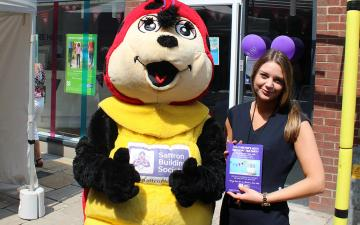 mage of a staff member standing with Miss Moneyspots. Saffron Building Society's mascot.